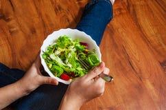 素食主义者在碗的早餐膳食用各种各样的新鲜的混合沙拉离开和蕃茄 拿着与膝盖和手visib的牛仔裤的女孩叉子 免版税库存图片