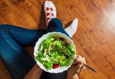 素食主义者在碗的早餐膳食用各种各样的新鲜的混合沙拉离开和蕃茄 拿着与膝盖和手visib的牛仔裤的女孩叉子 库存图片