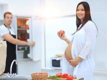 素食主义者愉快的怀孕的夫妇在厨房里 免版税库存图片