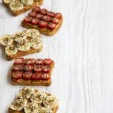 素食主义者敬酒用花生酱、果子和chia种子在白色木背景,低角度视图 选择聚焦 图库摄影