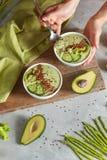 素食主义者点心用芦笋、黄瓜、鲕梨和flexseeds在妇女手上在石背景 免版税库存图片