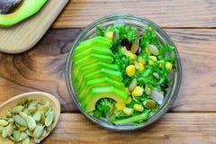 素食主义者鲕梨莴苣沙拉在一个玻璃碗和在一张木桌上 沙拉用鲕梨,莴苣叶子,装玉米于罐中 免版税库存图片