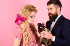 素食主义者 减速火箭的愉快的妇女和人举行野鸡 在桃红色的疯狂的夫妇 万圣节 创造性的想法 禽流感 滑稽 库存图片