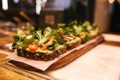 素食健康三明治用面包和向日葵种子用蕃茄和绿色在桌上 免版税库存图片