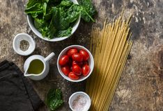 素食健康午餐的-整个五谷意粉面团,西红柿,在木背景的新鲜的菠菜,上面成份 库存图片