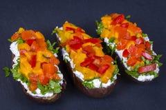素食健康食物-茄子充塞用乳脂干酪、绿色草本,烤红色和黄色胡椒在一黑板岩backgr 库存照片