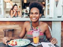 素食咖啡馆的美丽的混合的族种和平的岛民女孩与套的早餐和沙拉和新鲜的混合圆滑的人在玻璃 库存照片