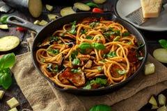 素食意大利面团意粉alla诺马用茄子、蕃茄、蓬蒿和帕尔马干酪在土气长柄浅锅平底锅 免版税库存图片
