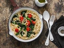 素食整个五谷意粉面团用西红柿和菠菜在木背景,顶视图的一个生铁平底锅调味 图库摄影