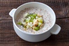 素食早餐:牛奶燕麦粥用香蕉、梨和猕猴桃sl 免版税库存照片