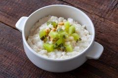 素食早餐:米牛奶粥用香蕉、梨和k 免版税库存图片