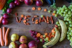 素食者和果子拼写在木桌上的素食主义者 免版税图库摄影