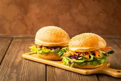 素食者汉堡由新鲜的芝麻小圆面包和未加工的蔬菜和年轻新芽做了在木土气土气背景 免版税库存照片