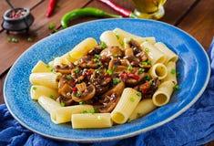 素食面团rigatoni用蘑菇和辣椒在蓝色碗 库存照片
