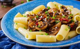 素食面团rigatoni用蘑菇和辣椒在蓝色碗 库存图片