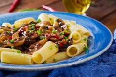 素食面团rigatoni用蘑菇和辣椒在蓝色碗 免版税库存照片