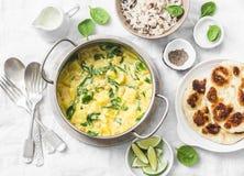 素食鸡豆、菠菜、土豆咖喱平底锅和naan小面包干在白色背景,顶视图 印地安健康食物 免版税库存照片