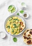 素食鸡豆、菠菜、土豆咖喱板材和naan小面包干在白色背景,顶视图 库存照片
