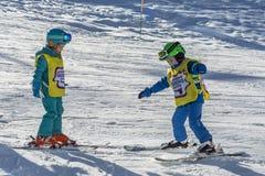 索契,俄罗斯,10-01-2018 罗莎Khutor滑雪胜地 一个男孩和一个女孩从一个小组山滑雪训练火车互相 免版税库存图片