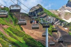 索契,俄罗斯- 2015年7月14日:年轻夫妇在椅子缆绳在高加索山脉的滑雪电缆车乘坐在晴朗的夏日 免版税图库摄影