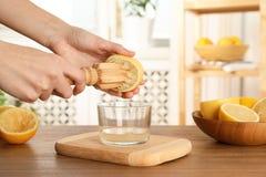 紧压与木绞刀的妇女柠檬汁入玻璃碗 免版税图库摄影
