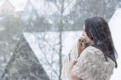 紧压她的披肩享用雪的妇女 库存照片