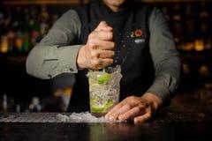 紧压新鲜的汁液的侍酒者从做Caipirinha鸡尾酒的石灰 库存图片