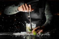 紧压新鲜的汁液的侍酒者手从做Caipirinha的石灰 免版税库存图片