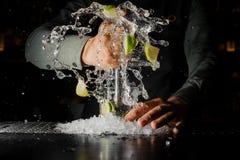 紧压新鲜的汁液的男服务员从做Caipirinha cocktai的石灰 免版税图库摄影