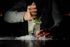 紧压汁液从新鲜的石灰使用柑橘新闻和飞溅它的侍酒者  免版税库存照片