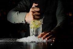 紧压汁液从新鲜的石灰使用柑橘新闻和飞溅它的男服务员  免版税库存照片