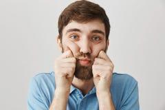 紧压面颊用手和看照相机的阴沉的翻倒有胡子的男性特写镜头画象,是在坏心情 免版税库存照片