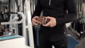 紧固他的保护传送带的人练习在健身房的大量的举重 股票视频