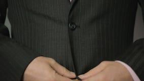紧固在他的夹克的衣服的办公室工作者上部和更低的按钮,关闭  股票视频
