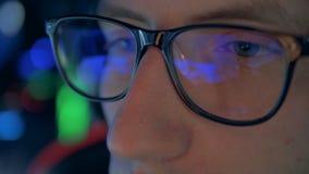 紧密与反射在他们的计算机游戏的游戏玩家的玻璃 影视素材