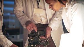 紧密在主板改善的工程师的团队工作在实验室