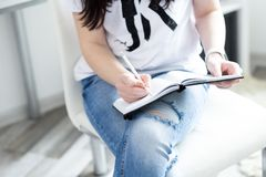 紧密妇女的在白色现代椅子安置的笔记薄的手文字,自由职业者 库存照片
