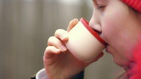 紧密,在春天森林,喝从热水瓶的少年女孩茶 从热水瓶杯子的旅客女孩倾吐的茶 股票视频