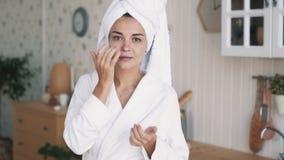紧密,有毛巾的女孩在头应用在她的面孔的润肤霜奶油,慢动作 股票录像