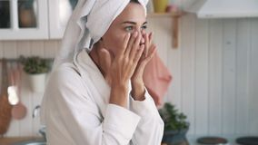 紧密,有毛巾的妇女在头应用在她的面孔的润肤霜奶油,慢动作 股票视频