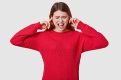 紧张深色头发的女性,佩带的红色套头衫照片,在恐慌,不要听见什么,感到绝望,隔绝 免版税库存照片