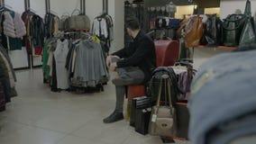 紧张的可爱的人坐椅子疲倦于等待他的姐妹从试装间出去开始谈在电话 股票录像