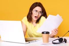 紧张的年轻深色的女商人照片与纸张文件一起使用在黄色背景的办公室,检查 库存照片