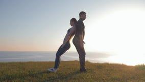 紧接同时蹲下在山的运动夫妇反对一个美好的风景在日落期间 股票视频