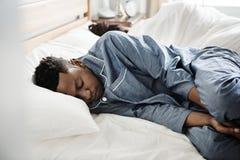 紧接睡觉在床上的夫妇 免版税库存照片