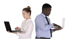 紧接站立和研究在白色背景的膝上型计算机的夫妇 图库摄影