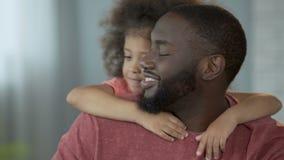 紧紧拥抱她的爸爸的逗人喜爱的女孩在脖子上用她小的手,柔软 影视素材
