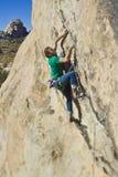紧贴的峭壁登山人 免版税库存照片