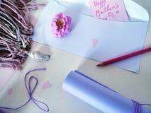 紫外纸、一个白色信封、一支红色铅笔和一只淡色蜡笔卷祝贺的在母亲` s天 免版税库存图片