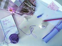 紫外纸、一个白色信封、一支红色铅笔和一只淡色蜡笔卷祝贺的在母亲` s天 图库摄影
